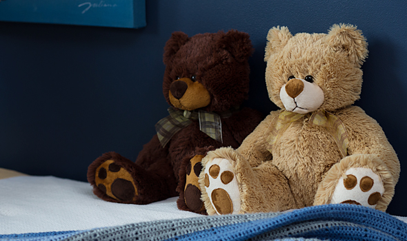Bears sitting on a bed